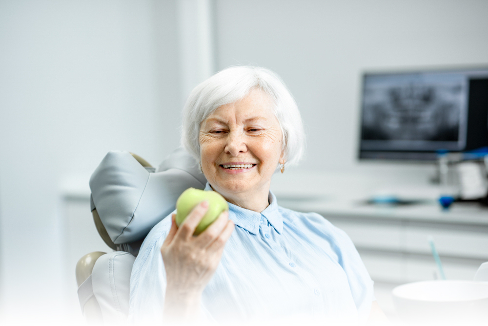 Older woman smiling eating an apple